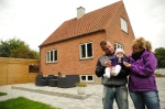 Happy family in front of house